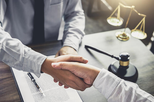 Hiring an attorney. Two people shaking hands.